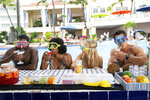 """This image released by Hulu shows Lil Rel Howery, from left, Yvonne Orji, Meredith Hagner and John Cena in a scene from """"Vacation Friends."""" (Jessica Miglio/20th Century Studios)"""