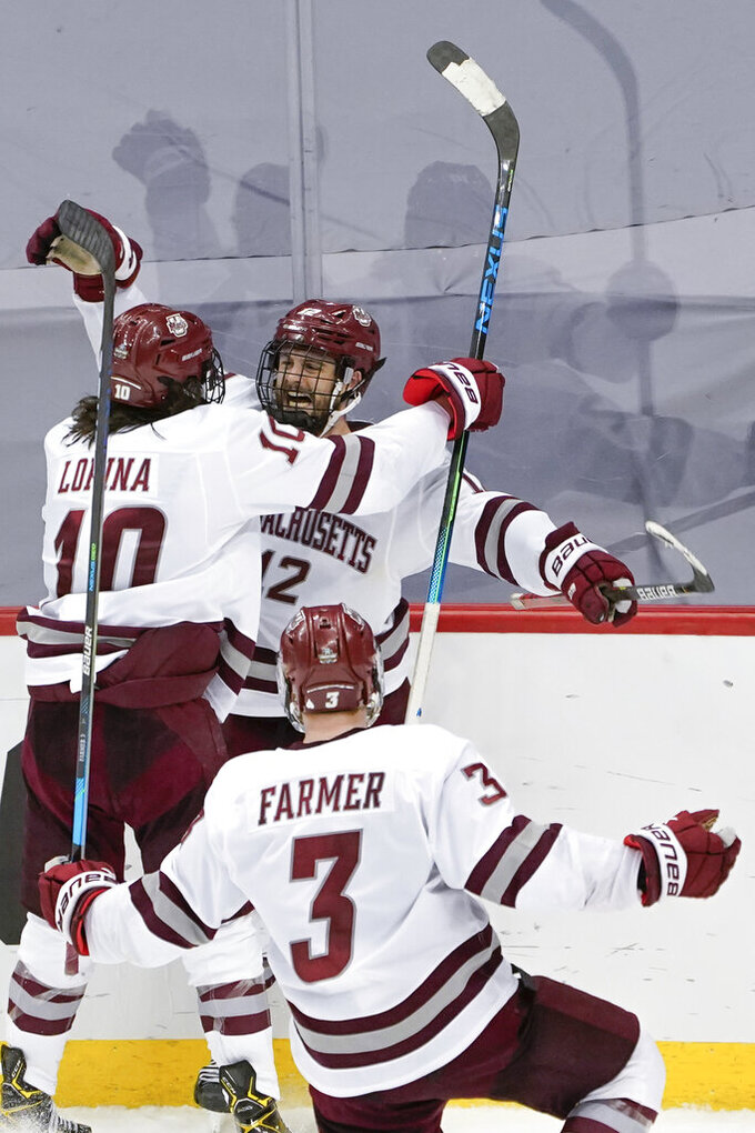 Massachusetts' Garrett Wait (12) celebrates with Josh Lopina (10) and Ty Farmer (3) after scoring in overtime against Minnesota Duluth in an NCAA men's Frozen Four hockey semifinal in Pittsburgh, early Friday, April 9, 2021. Massachusetts won 3-2 and will face St. Cloud State in the championship game Saturday. (AP Photo/Keith Srakocic)