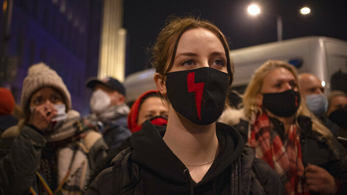Demonstrators wear masks with the red lightning bold, a symbol of the pro-choice movement, during a protest against a top court ruling restricting abortions in Warsaw, Poland, Wednesday, Nov. 18, 2020. The upheaval began when the constitutional court, packed with loyalists of the conservative ruling party, ruled Oct. 22 to ban abortions in cases of congenital fetal defects, even if the fetus has no chance of survival. (AP Photo/Agata Grzybowska)
