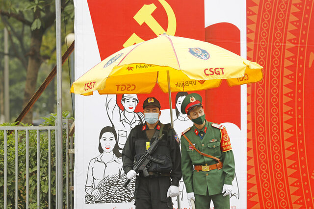 Vietnamese policemen wearing face masks stand guard outside the National Convention Center in Hanoi, Vietnam, Tuesday, Jan. 26, 2021. Vietnam's ruling Communist Party began a crucial week-long meeting in the capital Hanoi to set the nation's path for the next five years and appoint the country's top leaders. (AP Photo/Minh Hoang)