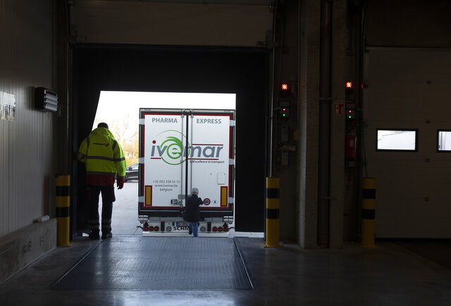 A worker waits as a truck pulls up to a temperature controlled warehouse at Swissport Pharma Center in Machelen, Belgium, Wednesday, Nov. 25, 2020. Safely delivering COVID-19 vaccines, once approval has been made, will be the mission of the century for the global air cargo industry. The Swissport Pharma Center, which opened in Oct. 2019, has a state of the art temperature controlled warehouse space dedicated specifically to pharmaceutical shipments going out of Brussels airport. (AP Photo/Virginia Mayo)