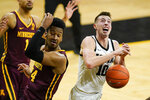Iowa guard Joe Wieskamp (10) loses the ball in front of Minnesota forward Eric Curry during the second half of an NCAA college basketball game, Sunday, Jan. 10, 2021, in Iowa City, Iowa. Iowa won 86-71. (AP Photo/Charlie Neibergall)
