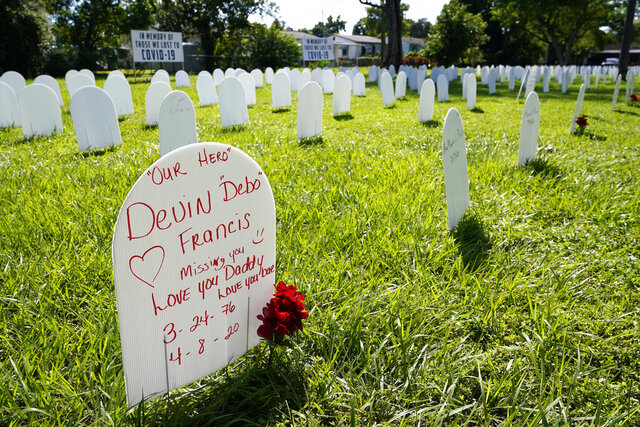 White plastic tombstone-shaped pieces are lined up as part of a temporary memorial to some of Miami's victims of the coronavirus at Simonhoff Floral Park, Wednesday, Oct. 14, 2020, in the Liberty City neighborhood of Miami. (AP Photo/Lynne Sladky)