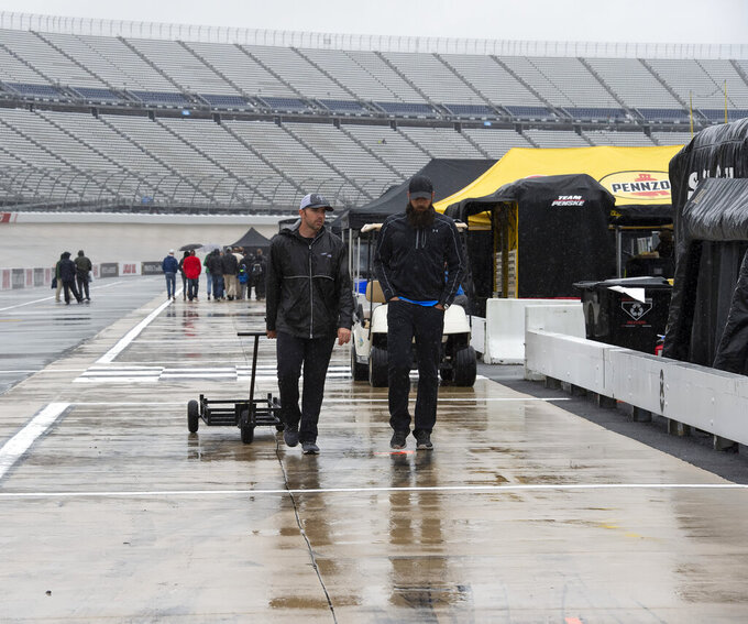 People walk in the pits area as rain falls before a NASCAR Cup series auto race at Dover International Speedway in Dover, Del., Sunday, May 5, 2019. (AP Photo/Jason Minto)