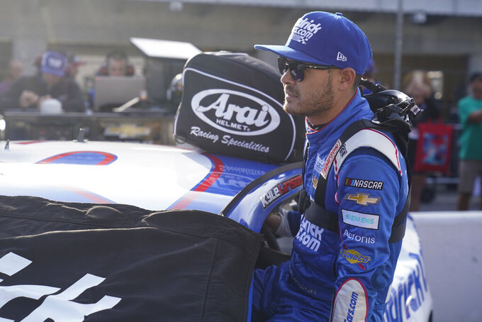 Kyle Larson climbs into his car before qualifications for the NASCAR Series auto race at Indianapolis Motor Speedway, Sunday, Aug. 15, 2021, in Indianapolis. (AP Photo/Darron Cummings)