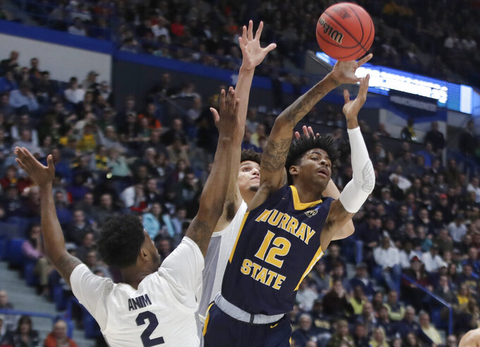 Murray State's Ja Morant (12) passes the ball under pressure from Marquette's Sacar Anim (2) and Brendan Bailey, behind, during the first half of a first round men's college basketball game in the NCAA Tournament, Thursday, March 21, 2019, in Hartford, Conn. (AP Photo/Elise Amendola)