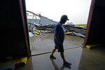 Jarod Voisin walks through damage of his family's heavily damaged oyster processing plant, as rain from Tropical Storm Nicholas, currently in the Gulf of Mexico, comes down, in the aftermath of Hurricane Ida in Houma, La., Tuesday, Sept. 14, 2021. (AP Photo/Gerald Herbert)