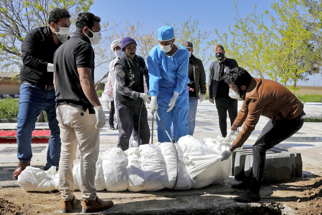 People wearing protective clothings, masks and gloves, attend the funeral of a victim who died after being infected with the new coronavirus, at a cemetery just outside Tehran, Iran, Monday, March 30, 2020.The new coronavirus causes mild or moderate symptoms for most people, but for some, especially older adults and people with existing health problems, it can cause more severe illness or death. (AP Photo/Ebrahim Noroozi)
