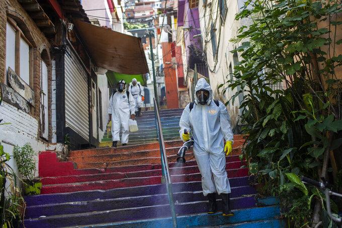 Thiago Firmino, right, sprays disinfectant to help contain the spread of the new coronavirus, in the Santa Marta slum of Rio de Janeiro, Brazil, Saturday, April 24, 2021. (AP Photo/Bruna Prado)