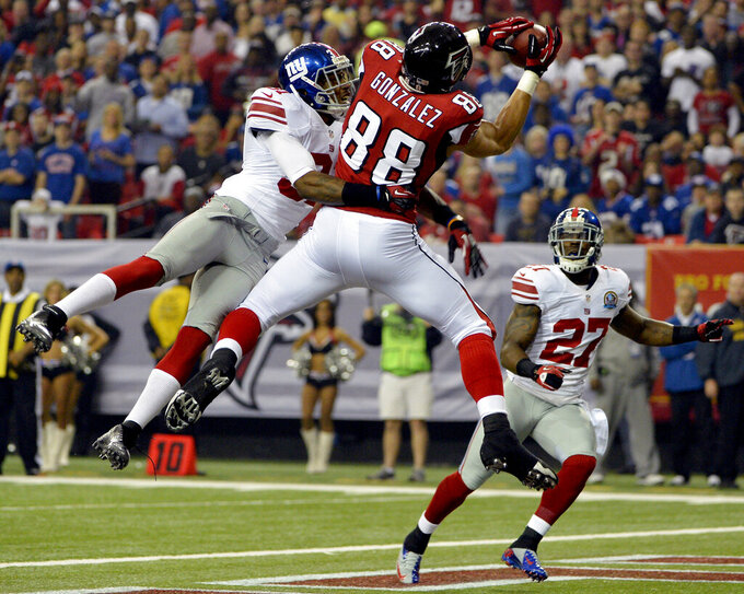 FILE - In this Dec. 16, 2012, file photo, Atlanta Falcons tight end Tony Gonzalez (88) makes a catch in the end zone for a touchdown as New York Giants defensive back Will Hill (31) and strong safety Stevie Brown (27) defend during the first half of an NFL football game, in Atlanta.  It was the ability of Gonzalez to make those tough catches, especially on third downs and in the red zone, that helped make him a first-ballot pick who will be inducted into the Pro Football Hall of Fame on Aug. 3, 2019. (AP Photo/Rich Addicks, File)