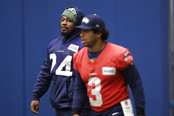 Seattle Seahawks running back Marshawn Lynch, left, looks across at quarterback Russell Wilson during warmups at the NFL football team's practice facility Tuesday, Dec. 24, 2019, in Renton, Wash. When Lynch played his last game for the Seahawks in 2016, the idea of him ever wearing a Seahawks uniform again seemed preposterous. Yet, here are the Seahawks getting ready to have Lynch potentially play a major role Sunday against San Francisco with the NFC West title on the line. (AP Photo/Elaine Thompson)