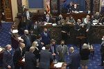 In this Feb. 10, 2021, image from video, Senate parliamentarian Elizabeth MacDonough, seated in the back second row third from right, talks as senators gather in the foreground around Senate Majority Leader Chuck Schumer of N.Y., and House impeachment manager Rep. Jamie Raskin, D-Md., bottom left, during the second impeachment trial of former President Donald Trump in the Senate at the U.S. Capitol in Washington. MacDonough has guided the Senate through two impeachment trials, vexed Democrats and Republicans alike with parliamentary opinions and helped rescue Electoral College certificates from a pro-Trump mob ransacking the Capitol.(Senate Television via AP)