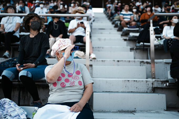 Limited numbers of fans watch in the Fuji International Speedway during the men's cycling road race at the 2020 Summer Olympics, Saturday, July 24, 2021, in Oyama, Japan. (AP Photo/Thibault Camus)