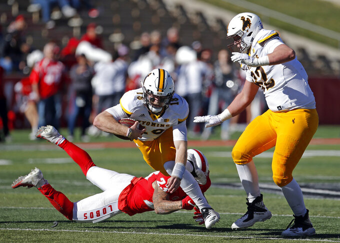 Wyoming quarterback Tyler Vander Waal (18) is stumbled by New Mexico linebacker Jordan Flack (29) as Wyoming offensive tackle Rudy Stofer (62) looks on during the first half of an NCAA college football game in Albuquerque, N.M., Saturday, Nov. 24, 2018. (AP Photo/Andres Leighton)