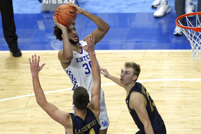 Kentucky's Olivier Sarr, top, shoots while over Notre Dame's Nate Laszewski, bottom, and Dane Goodwin during the second half of an NCAA college basketball game in Lexington, Ky., Saturday, Dec. 12, 2020. Notre Dame won 64-63. (AP Photo/James Crisp)