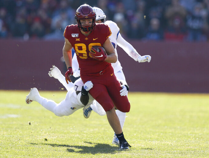 Iowa State tight end Charlie Kolar, center, runs the ball as he is tackled by Kansas safety Davon Ferguson during the first half of an NCAA college football game, Saturday, Nov. 23, 2019, in Ames, Iowa. (AP Photo/Matthew Putney)