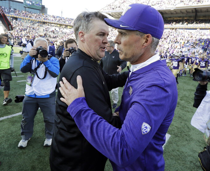 Washington head coach Chris Petersen, right, greets Colorado head coach Mike MacIntyre, left, following an NCAA college football game, Saturday, Oct. 20, 2018, in Seattle. Washington won 27-13. (AP Photo/Ted S. Warren)
