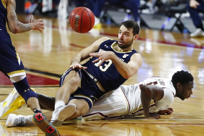 Notre Dame's Nikola Djogo (13) falls on Boston College's Jay Heath (5) during the second half of an NCAA college basketball game, Saturday, Feb. 27, 2021, in Boston. (AP Photo/Michael Dwyer)