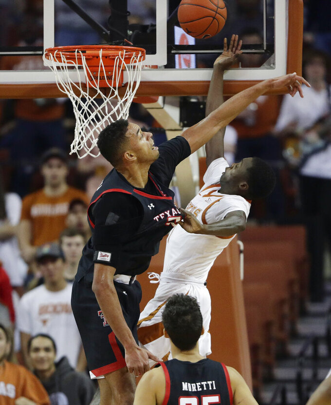 Texas guard Matt Coleman III, right, is blocked by Texas Tech guard Kyler Edwards, left, tduring the first half of an NCAA college basketball game, Saturday, Feb. 8, 2020, in Austin, Texas. (AP Photo/Eric Gay)