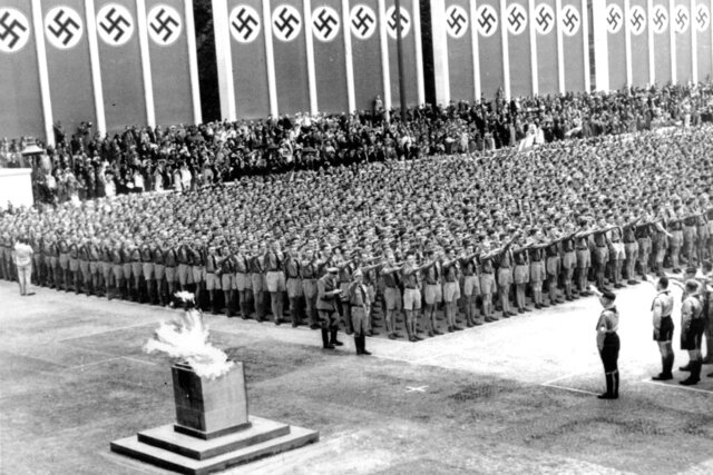 FILE - In this Aug. 1, 1936, file photo, German Nazi soldiers line up at attention during the opening ceremonies of the XI Summer Olympic Games at the Lustgarten in Berlin, Germany. The lighted Olympic torch is in the foreground. The torch relay was not always a fixture of the modern Olympics, which began in 1896. The relay tradition began with Adolph Hitler's 1936 Olympics in Berlin, the Games of the XI Olympiad, and was the brainchild of Dr. Carl Diem who was the head of the organizing committee. (AP Photo/File)