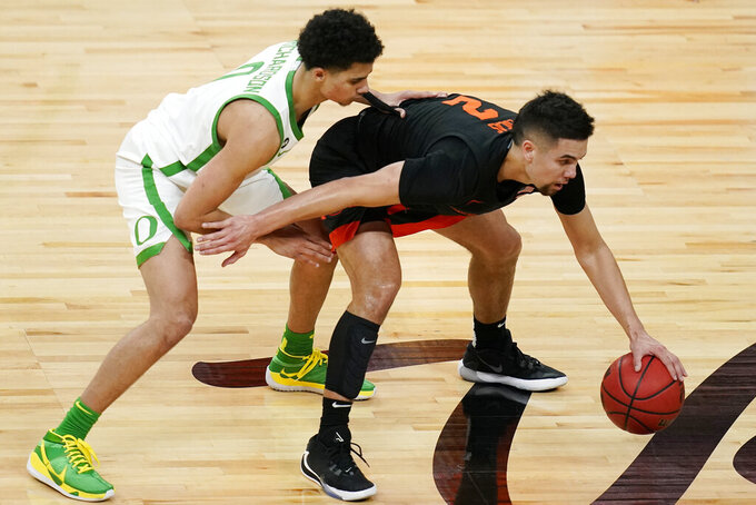 Oregon's Will Richardson, left, guards Oregon State's Jarod Lucas (2) during the first half of an NCAA college basketball game in the semifinal round of the Pac-12 men's tournament Friday, March 12, 2021, in Las Vegas. (AP Photo/John Locher)