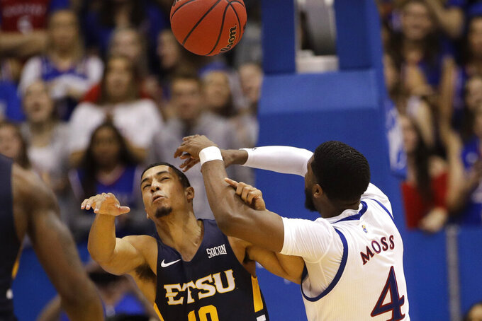 East Tennessee State guard Patrick Good (10) passes the ball over Kansas guard Isaiah Moss (4) during the second half of an NCAA college basketball game Tuesday, Nov. 19, 2019, in Lawrence, Kan. Kansas won 75-63. (AP Photo/Charlie Riedel)