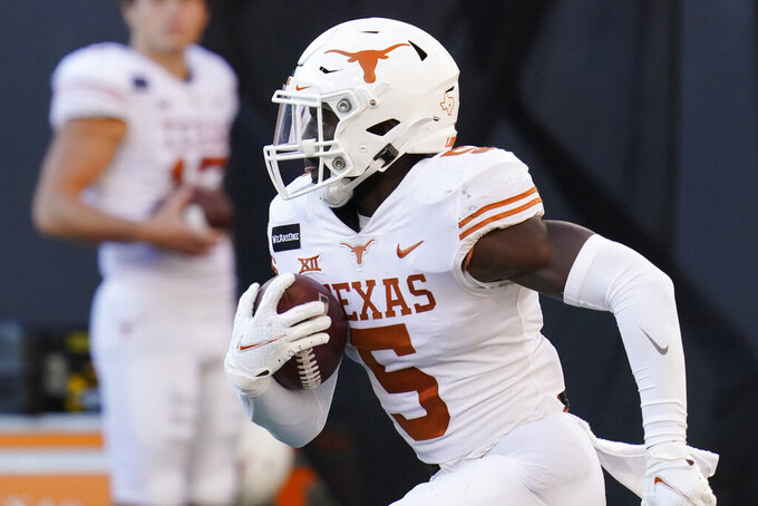 Texas' D'Shawn Jamison (5) begins his 100-yard kickoff return for a touchdown during the second half of the team's NCAA college football game against Oklahoma State in Stillwater, Okla., Saturday, Oct. 31, 2020. (AP Photo/Sue Ogrocki)