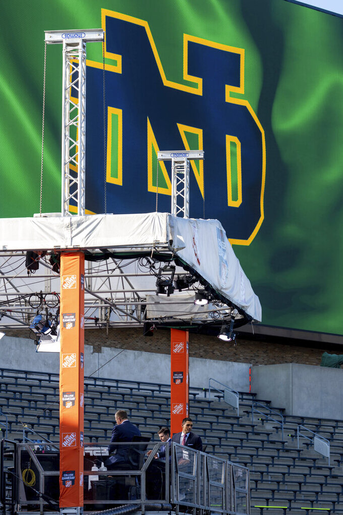 ESPN College Gameday host David Pollack, right, looks out toward the field as they prepare for their live broadcast from Notre Dame Stadium before the NCAA college football game between the Notre Dame and the Clemson in South Bend, Ind. (Matt Cashore/Pool Photo via AP)