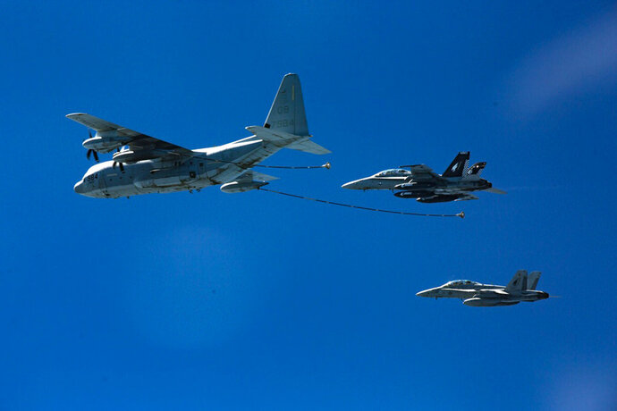 In this Oct. 13, 2016, photo provided by U.S. Marine Corps, two F/A-18D Hornets with Marine All-Weather Fighter Attack Squadron 533 approach a KC-130J with Marine Aerial Refueler Transport Squadron 352 during a Special Purpose Marine Air-Ground Task Force - Crisis Response - Central Command aerial refueling exercise in undisclosed location.  On Thursday, Dec. 6, 2018, two American warplanes crashed into the Pacific Ocean off Japan's southwestern coast after a midair collision,  and rescuers found one of the seven crew members in stable condition while searching for the others, officials said.  The U.S. Marine Corps said that the crash involved an F/A-18 fighter jet and a KC-130 refueling aircraft during regular training after the planes took off from their base in Iwakuni, near Hiroshima in western Japan.  (Cpl. Trever Statz/U.S. Marine Corps via AP)