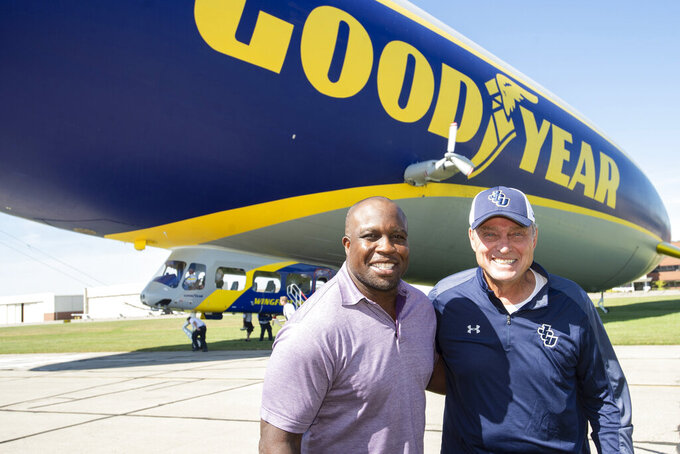 FILE - In this Friday, Sept. 27, 2019, file photo, College Football Hall of Fame inductee London Fletcher, left, and his high school and college coach Mike Moran pose following their surprise reunion and ride on the Goodyear Blimp in Cleveland. It's been an emotional whirlwind lately for Fletcher, who was enshrined last week in the Washington Redskins' Ring of Honor. He'll soon become a member of the College Football Hall of Fame — inducted along with Goodyear's iconic blimp, the first non-player or coach elected. (AP Photo/Phil Long, File)