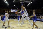 San Diego guard Olin Carter III, center, passes to teammate forward Yauhen Massalski, left, during the first half of an NCAA college basketball game against Brigham Young Thursday, Feb. 14, 2019, in San Diego. (AP Photo/Gregory Bull)
