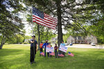 The Lagoy Family of Guilford, Maine, await the arrival of President Donald Trump, Friday, June 5, 2020, in Guilford. Trump is scheduled to visit Puritan Medical Products Co., one of the top two makers of testing swabs in the world. (AP Photo/Robert F. Bukaty)