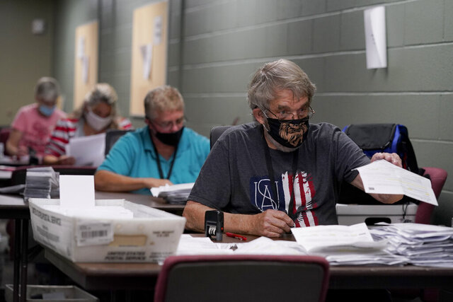 Election workers open and sort mail-in ballot requests Tuesday, Sept. 22, 2020, at the Johnson County election office in Olathe, Kan. The office has processed more than 100,000 mail-in ballot requests so far as more people than normal are expected to vote by mail due to concerns about the coronavirus. (AP Photo/Charlie Riedel)