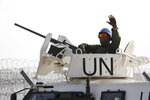 A UN soldier waves as UN vehicle enters Syria in Quneitra crossing in the Israeli controlled Golan Heights , Monday, Oct. 15, 2018. The crossing between Syria and the Israeli-occupied Golan Heights reopened for U.N. observers who had left the area four years ago because of the fighting there. (AP Photo/Ariel Schalit)