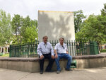 In this Monday, June 14, 2021, photo, Union Protectíva de Santa Fé president Virgil Vigil and vice president Richard Varela sit in front of the covered remnants of the Soldier's Memorial obelisk at the center of the Plaza in Santa Fe, N.M. Their Hispanic cultural association Union Protectíva de Santa Fé sued the city's mayor Wednesday, June 16, over the destruction of the obelisk by activists the year before, and plans to permanently move the memorial. The lawsuit argues that the obelisk, which honors Hispanic soldiers that fought and died for the Union in battles with Confederate soldiers and Indigenous tribes, is a protected historical site. (AP Photo/Cedar Attanasio)