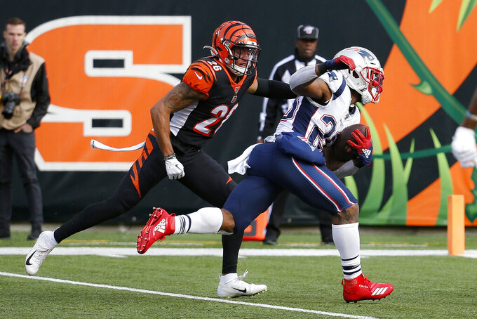 New England Patriots running back James White, right, runs the ball in for a touchdown against Cincinnati Bengals cornerback Greg Mabin (26) in the first half of an NFL football game, Sunday, Dec. 15, 2019, in Cincinnati. (AP Photo/Frank Victores)