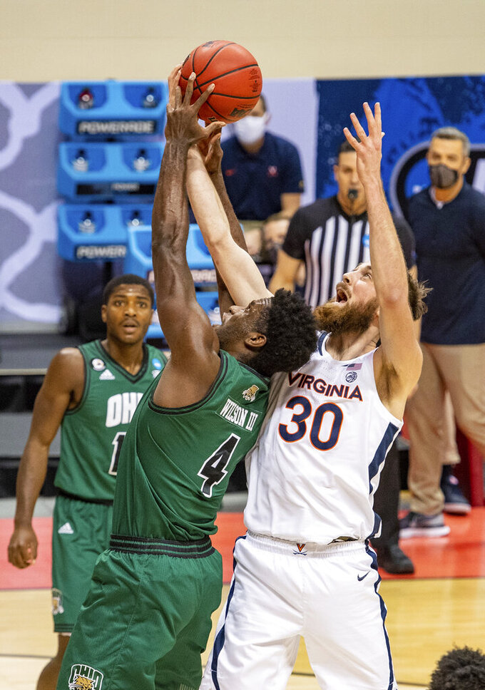 Ohio forward Dwight Wilson III (4) and Virginia forward Jay Huff (30) battle for a rebound during the first half of a first-round game in the NCAA men's college basketball tournament, Saturday, March 20, 2021, at Assembly Hall in Bloomington, Ind. (AP Photo/Doug McSchooler)