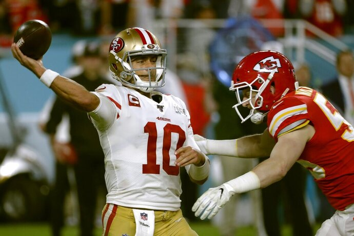 San Francisco 49ers' quarterback Jimmy Garoppolo passes under pressure from Kansas City Chiefs' Ben Niemann, right, during the second half of the NFL Super Bowl 54 football game Sunday, Feb. 2, 2020, in Miami Gardens, Fla. (AP Photo/Matt York)