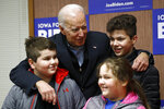 Democratic presidential candidate, former Vice President Joe Biden visits with siblings Adi Skrgic, age 11, from left, Edna Skrgic, age 8, and Dino Skrgic, age 13, during a visit to a campaign field office, Saturday, Jan. 4, 2020, in Waterloo, Iowa. (AP Photo/Patrick Semansky)