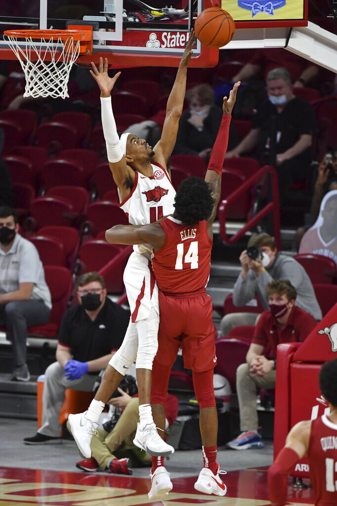Arkansas guard Jalen Tate (11) blocks the shot of Alabama guard Keon Ellis (14) during the first half of an NCAA college basketball game in Fayetteville, Ark. Wednesday, Feb. 24, 2021. (AP Photo/Michael Woods)