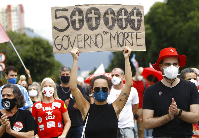 """A woman wearing a protective face mask holds a sign with a message that reads in Portuguese; """"500,000, government of death"""" during a protest against Brazilian President Jair Bolsonaro's handling of the coronavirus pandemic and economic policies they say harm the interests of the poor and working class, in Rio de Janeiro, Brazil, Saturday, June 19, 2021. Brazil is approaching an official COVID-19 death toll of 500,000 — second-highest in the world. (AP Photo/Bruna Prado)"""