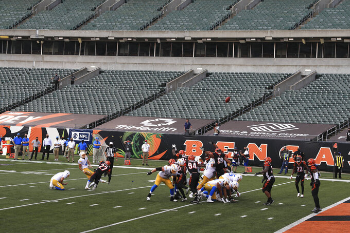 FILE—In this file photo from Sept. 13, 2020, Los Angeles Chargers kicker Mike Badgley (4) boots a field goal out of the hold of Ty Long (1) at Paul Brown stadium that is devoid of fans during the second half of an NFL football game against the Cincinnati Bengals, in Cincinnati. About one in six Ohio school districts asked the state for permission to add additional spectators for fall sporting events, exceeding the limits set by  Gov. Mike DeWine in last month's sports order, records show.  (AP Photo/Aaron Doster, File)