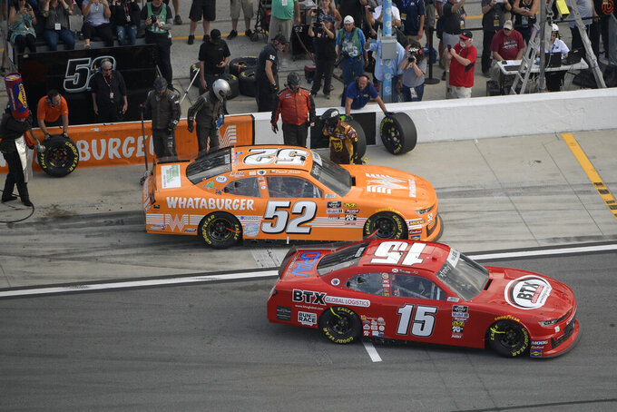 David Starr (52) and BJ McLeod (15) leave pit road during a NASCAR Xfinity Series auto race at Daytona International Speedway Saturday, Feb. 16, 2019, in Daytona Beach, Fla. (AP Photo/Phelan M. Ebenhack)