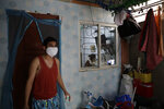 Christopher Bagay, left, a kitchen crew of the Aida Sol cruise ship in Europe, walks outside their house as his wife, right, continues her work from home duty at their house in Laguna province, south of Manila, Philippines Thursday, May 28, 2020. Bagay said it took him about two months to go through repetitive quarantines in Spain, Germany and Manila before he was finally allowed to go home. Tens of thousands of workers have returned by plane and ships as the pandemic, lockdowns and economic downturns decimated jobs worldwide in a major blow to the Philippines, a leading source of global labor. (AP Photo/Aaron Favila)