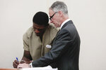 Attorney Sam Shamansky, right, helps former Ohio State Buckeyes football player Jahsen Wint as he fills out paperwork during his arraignment on Thursday, Feb. 13, 2020 at the Franklin County Municipal Courthouse in Columbus, Ohio. Wint, who was dismissed from the team on Feb. 12, 2020, along with teammate and co-defendant Amir Riep, are charged with the rape and kidnapping of a 19-year-old woman on Feb. 4, 2020 at an apartment the two men share. (Joshua A. Bickel/The Columbus Dispatch via AP)