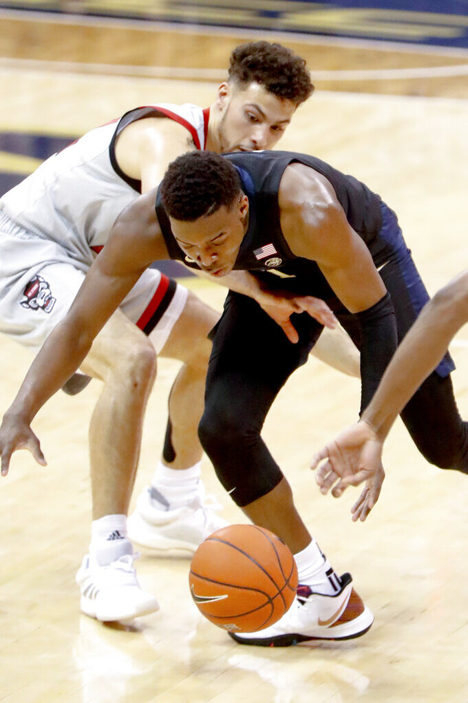 North Carolina State's Devon Daniels, left, reaches into Pittsburgh's Xavier Johnson as he brings the ball up the court during the first half of an NCAA college basketball game, Saturday, Feb. 9, 2019, in Pittsburgh. Johnson was called for travelling on the play. (AP Photo/Keith Srakocic)