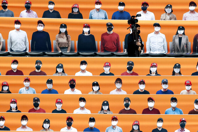 A TV cameraman walks through the spectators' seating which are covered with pictures of fans, before the start of a regular season baseball game between Hanwha Eagles and SK Wyverns in Incheon, South Korea, Tuesday, May 5, 2020. South Korea's professional baseball league start its new season on May 5, initially without fans, following a postponement over the coronavirus. (AP Photo/Lee Jin-man)