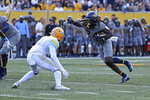 West Virginia running back Tony Mathis Jr. (24) is defended by Long Island safety Derrick Edafe during the first half of an NCAA college football game in Morgantown, W.Va., Saturday, Sept., 11, 2021. (AP Photo/Kathleen Batten)