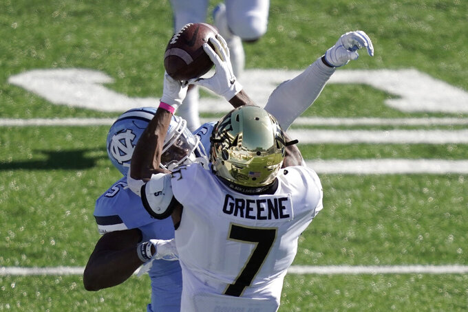 Wake Forest wide receiver Donavon Greene (7) catches a pass while North Carolina defensive back Patrice Rene (5) defends during the first half of an NCAA college football game in Chapel Hill, N.C., Saturday, Nov. 14, 2020. (AP Photo/Gerry Broome)
