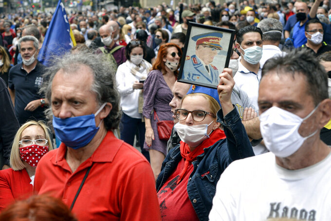 A woman holds a portrait of Yugoslav leader Josip Broz Tito, as people attend an anti-Nazi protest outside the Sacred Heart Cathedral during a mass commemorating members of the pro-Nazi Croatian WWII Ustasha regime, responsible for sending tens of thousands of Serbs, Gypsies and Jews to their death in concentration camps, who were killed at the end of WWII by Yugoslav communist troops, in Sarajevo, Bosnia, Saturday, May 16, 2020. Bosnian Catholic clerics along with Croatian state representatives and members of the Bosnian Croats community attended a religious service commemorating the massacre of Croatian pro-Nazis by victorious communists at the end of World War II. (AP Photo/Kemal Softic)
